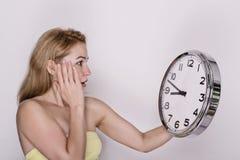 Mujer hermosa joven que sostiene el reloj grande Mida el tiempo del concepto Fotografía de archivo libre de regalías