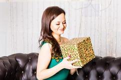 Mujer hermosa joven que sostiene la caja de regalo en una Noche Vieja Interior con las decoraciones de la Navidad Imagenes de archivo