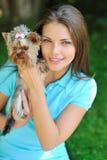 Mujer hermosa joven que sostiene su perro de perrito - retrato al aire libre Imagenes de archivo