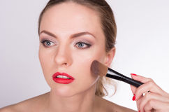 Mujer hermosa joven que sostiene un cepillo y que aplica su maquillaje Imagen de archivo libre de regalías