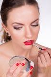 Mujer hermosa joven que sostiene un cepillo y que colorea sus labios Fotografía de archivo libre de regalías