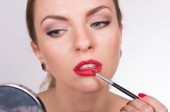 Mujer hermosa joven que sostiene un cepillo y que colorea sus labios Imagenes de archivo