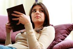 Mujer hermosa joven que sostiene un libro y que mira lejos Imagen de archivo libre de regalías