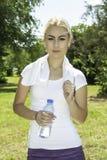 Mujer hermosa joven que sostiene una botella de agua Fotos de archivo libres de regalías