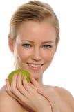 Mujer hermosa joven que sostiene una manzana verde Fotografía de archivo libre de regalías