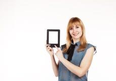 Mujer hermosa joven que sostiene una tableta foto de archivo