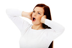 Mujer hermosa joven que tapa sus oídos y que grita Fotos de archivo