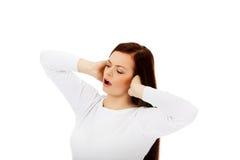 Mujer hermosa joven que tapa sus oídos y que grita Fotografía de archivo libre de regalías