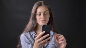 Mujer hermosa joven que tiene charla video a través del teléfono celular, hablando y sonriendo, aislado en fondo negro almacen de video