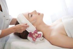Mujer hermosa joven que tiene masaje facial Imágenes de archivo libres de regalías