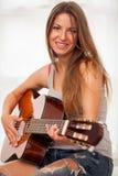 Mujer hermosa joven que toca la guitarra Imagenes de archivo
