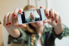 Mujer hermosa joven que toma un selfie con smartphone en ella nueva Fotografía de archivo libre de regalías
