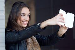 Mujer hermosa joven que toma un selfie en la calle Imagenes de archivo