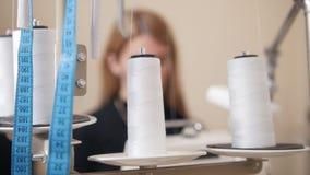 Mujer hermosa joven que trabaja con la máquina de coser en fábrica Metro en el marco metrajes