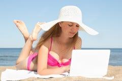 Mujer hermosa joven que trabaja en el ordenador portátil blanco en la playa Fotos de archivo
