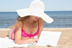 Mujer hermosa joven que trabaja en el ordenador portátil en la playa Imagenes de archivo
