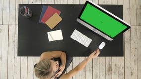 Mujer hermosa joven que trabaja y que habla con el teléfono elegante y que usa el ordenador Exhibición verde de la maqueta de la  metrajes