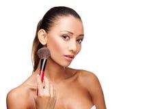 Mujer hermosa joven que usa el cepillo para aplicar maquillaje Imágenes de archivo libres de regalías