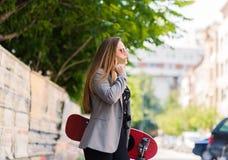 Mujer hermosa joven que usa el teléfono celular mientras que sostiene el monopatín Imagenes de archivo