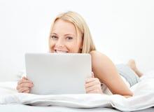Mujer hermosa joven que usa la computadora portátil en cama Fotos de archivo