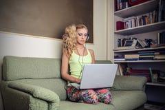 Mujer hermosa joven que usa su ordenador portátil Imagen de archivo