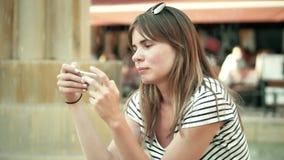 Mujer hermosa joven que usa su smartphone cerca de la fuente almacen de metraje de vídeo