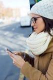 Mujer hermosa joven que usa su teléfono móvil en un autobús Imágenes de archivo libres de regalías