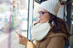 Mujer hermosa joven que usa su teléfono móvil en un autobús Foto de archivo libre de regalías