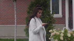 Mujer hermosa joven que usa su teléfono móvil que camina en la calle al aire libre almacen de video