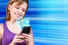 Mujer hermosa joven que usa un smartphone Fotos de archivo libres de regalías