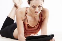Mujer hermosa joven que usa una tableta después de entrenamiento fotos de archivo libres de regalías