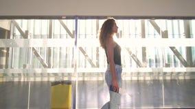 Mujer hermosa joven que va al avión de embarque en el terminal de aeropuerto metrajes