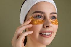 Mujer hermosa joven sonriente en los remiendos del oro para los ojos en fondo verde imagen de archivo