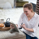 Mujer hermosa joven sonriente que disfruta de comercio electrónico de la tableta casera Fotos de archivo