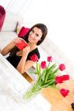 Mujer hermosa joven sonriente que goza de una taza de café Imagenes de archivo
