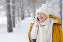 Mujer hermosa, joven, sonriente que habla en el smartphone Imagen de archivo libre de regalías