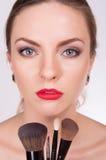 Mujer hermosa joven sosteniendo cepillos debajo de su cara Imágenes de archivo libres de regalías