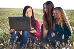 Mujer hermosa joven tres con una computadora portátil Foto de archivo