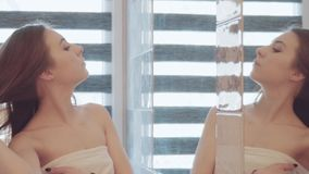Mujer hermosa joven watcing y que comprueba su cara en el espejo en cuarto de baño almacen de metraje de vídeo