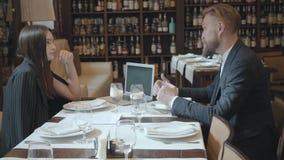 Mujer hermosa joven y hombre maduro con la barba que cena negocio con el ordenador portátil en restaurante Muchas botellas almacen de video