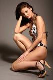 Mujer hermosa kneeing en traje de baño clásico Imagen de archivo libre de regalías