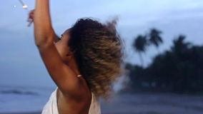 Mujer hermosa levantada que sostiene la bengala que celebra y que salta en la playa en la cámara lenta almacen de video