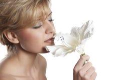 Mujer hermosa para oler la flor. cierre para arriba imagen de archivo