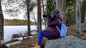 Mujer hermosa pensativa que toma imágenes en a cámara lenta de la naturaleza nevada metrajes