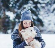 Mujer hermosa que abraza el perro blanco del terrier foto de archivo