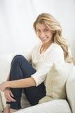 Mujer hermosa que abraza rodillas mientras que se sienta en el sofá Fotos de archivo libres de regalías
