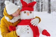 Mujer hermosa que abraza un muñeco de nieve Imagen de archivo libre de regalías