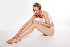 Mujer hermosa que acaricia sus piernas Imagenes de archivo