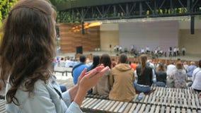 Mujer hermosa que aplaude en el concierto del aire abierto durante verano 4K metrajes