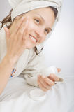 Mujer hermosa que aplica el krem facial Foto de archivo libre de regalías